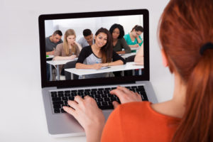 young lady in front of laptop learning online